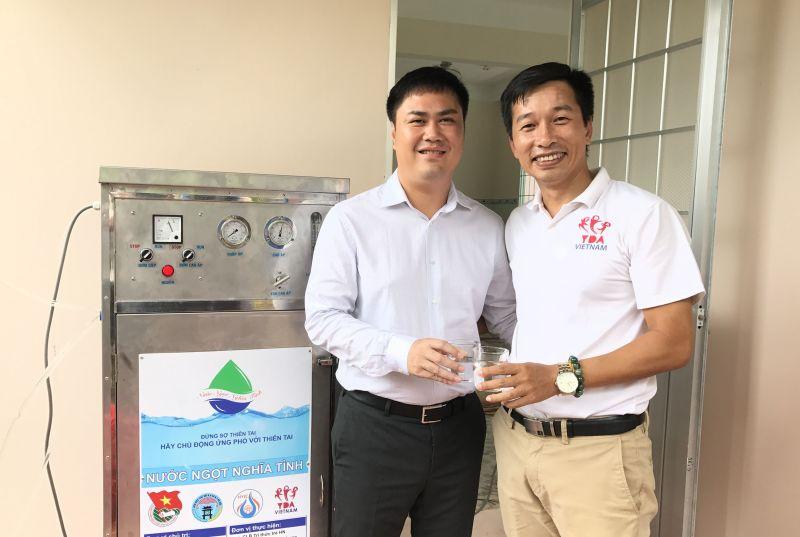 Đồng tổ chức chương trình, TS. Đỗ Minh Chính (trái) cùng Ông Trần Vũ Thành trực tiếp hướng dẫn sử dụng và uống những giọt nước được đưa ra từ máy.